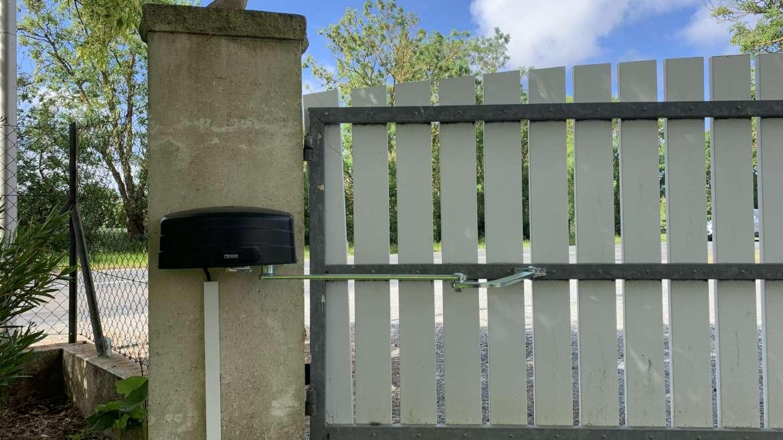 Installation d'une motorisation à bras grande envergure sur un portail existant de grande largeur.