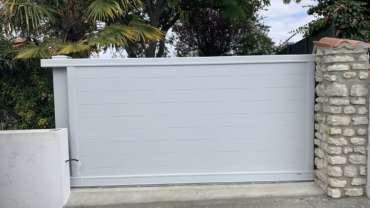 Pose portail coulissant plein aluminium avec poteau de guidage.